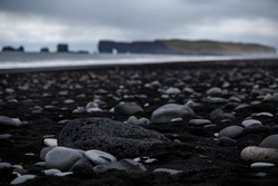 Volcanic rock on black sand beach at Vik in southern Iceland with eroded stone arch visible in distance