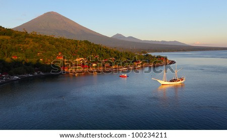 Volcano Agung (Bali island, Indonesia) lighted by rising sun and calm lagoon with sail boat