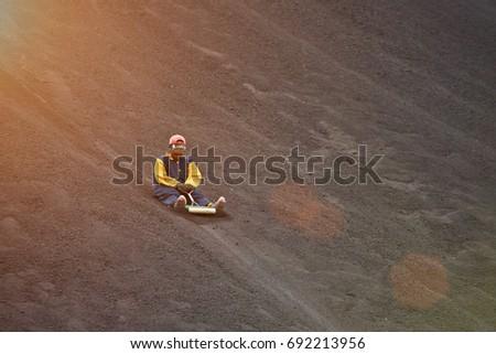 Volcano boarding in NIcaragua. Man riding board on volcano ash