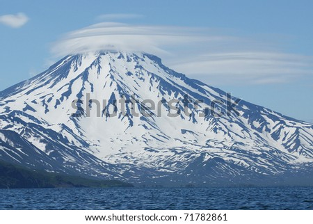 Volcano covered with snow and wearing a hat made of clouds. The heart-shaped cloud is above the volcano.