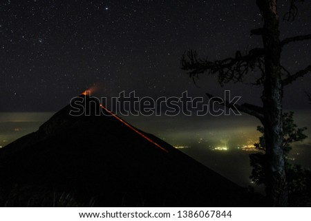 volcano fuego in antigua guatemala erupts during nighttime with nightsky #1386067844