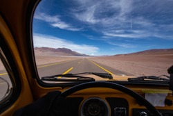 Volkswagen Beetle driver's view across a desert landscape