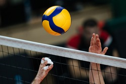 Volleyball action. Ball  above net during volleyball game.