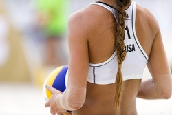 Volleyball beach player is a female athlete volley ball player getting ready to serve the ball.