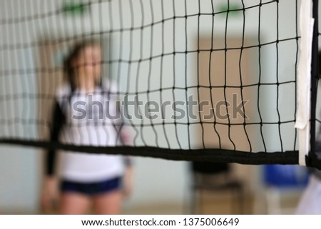 Volleyball net. In the background is a volleyball player, a girl