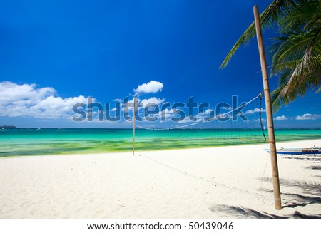Volleyball net on perfect white sand tropical beach - stock photo