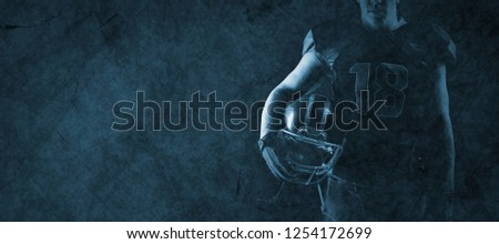 Volleyball player holding rugby helmet against old wall background