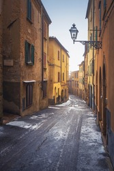 Volterra old town street during a snowfall in winter. Pisa province, Tuscany, Italy, Europe.