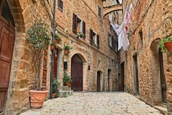 Volterra, Pisa, Tuscany, Italy: picturesque alley in the old town with ancient buildings and clothes hanging