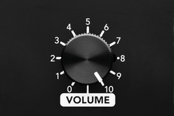 Volume control knob of a black amplifier on maximum loudness. Close up view with copy space.