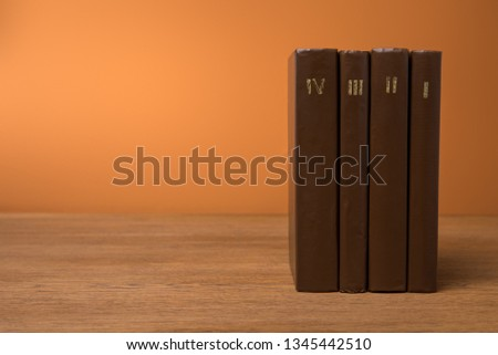 volumes of vintage books in leather brown covers on wooden table  #1345442510