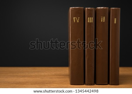 volumes of vintage books in leather brown covers on wooden table isolated on black #1345442498