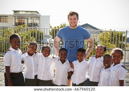 Volunteer and elementary school kids in playground, portrait