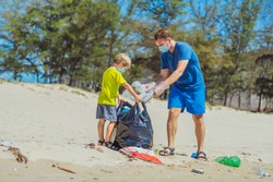 Volunteer blue face mask forest sand beach. Son helps father hold black bag for pick up garbage. Problem spilled rubbish trash planet pollution environmental protection. Natural children education