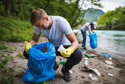 Volunteer cleaning garbage near river