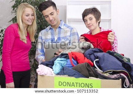 volunteer group with clothing donation and tablet