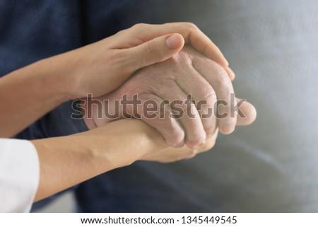 Volunteer holding hand of senior man, closeup