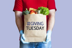 Volunteer in medical gloves holds paper grocery bag with inscription Giving tuesday on blue background. Charity, help and donation concept.
