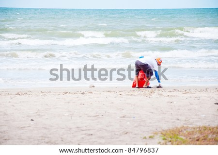 volunteer man cleaning on beach