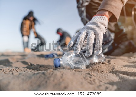 Volunteer man collecting trash on the beach. Ecology concept
