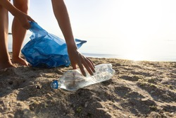 Volunteer Picking Up Plastic Bottle On Polluted Beach During Ocean Coastal Cleanup Outside. Cropped, Free Space For Text