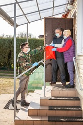 Volunteer / soldier brought food for senior citizens. Volunteer in a medical mask and gloves passes a bag of products to an elderly couple in masks on the steps. Coronavirus pandemic covid-19
