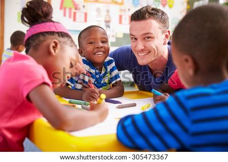 Volunteer teacher helping a class of preschool kids drawing