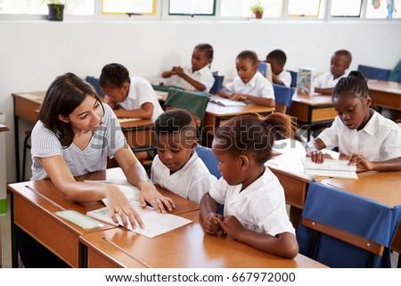 Volunteer teacher helping school kids at their desks