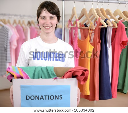 Volunteer with clothes donation box at second hand store