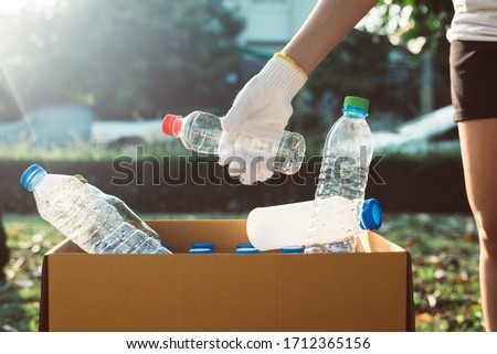 Volunteer woman keep plastic bottle into paper box at public park,Dispose recycle and waste management concept,Good conscious mind
