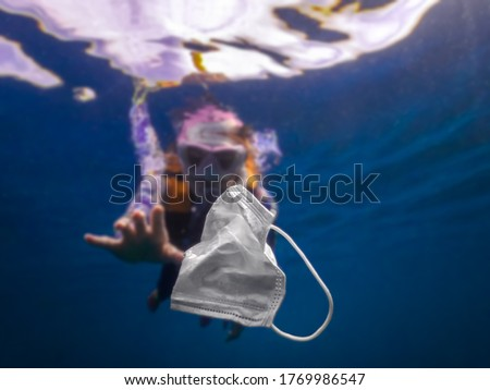 Volunteer woman scuba divers are exploring underwater and cleaning up the ocean. Catch a disposable masks outbreak trash on the blue water. Trash in the beach threatening the health of oceans. Foto stock ©