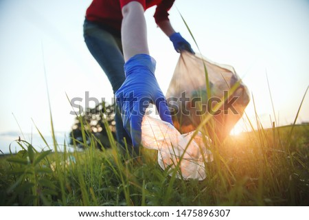 volunteer young woman collecting garbage, picking up waste at sunset light, land pollution, environmental problem Сток-фото ©