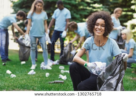 Volunteering, charity and clean environment concept. Happy black woman and group of volunteers with garbage bags cleaning area in park, copy space