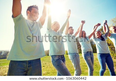 volunteering, charity and people concept - group of happy volunteers holding hands outdoors