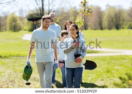 volunteering, charity, people and ecology concept - group of happy volunteers with tree seedlings and rake walking in park #512039929