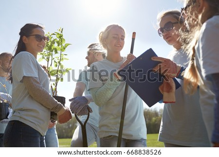volunteering, charity, people and ecology concept - group of happy volunteers with tree seedlings and clipboard in park