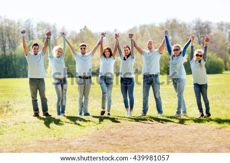 volunteering, charity, people, gesture and ecology concept - group of happy volunteers celebrating success up in park