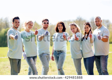volunteering, charity, people, gesture and ecology concept - group of happy volunteers showing thumbs up in park