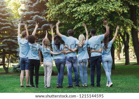 Volunteering, unity and charity. Group of volunteers embracing and gesturing in park, back view, copy space #1215144595