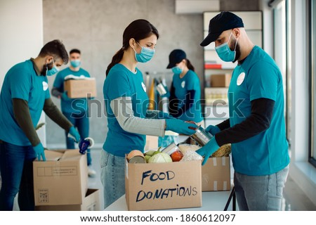 Volunteers cooperating while sorting food in donation boxes for charity food bank. Stock fotó ©