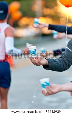 Volunteers hands offering water during a Marathon. Use of selective focus. Lots of Copyspace.