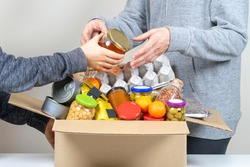 Volunteers hands putting grocery products, foodstuff to food donations box