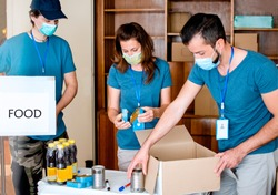 Volunteers Packing humanitarian aid in donation box. Group of people working in charitable foundation helping in crises and homeless.Donation and charity concept