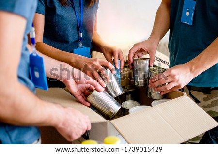 Volunteers Packing humanitarian aid in donation box. Group of people working in charitable foundation helping in crises and homeless. Donation and charity concept