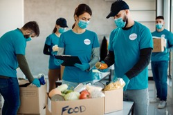 Volunteers wearing face masks while working in charitable foundation and packing donation boxes for food bank.