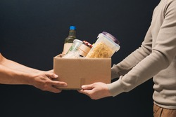 Volunteers with donation box with foodstuffs on dark background