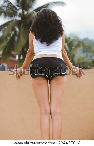 Voluptuous back of Indian female curves on the roof in natural lighting condition.