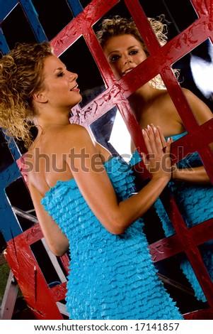 Voluptuous girl standing beside mirror in night club interior