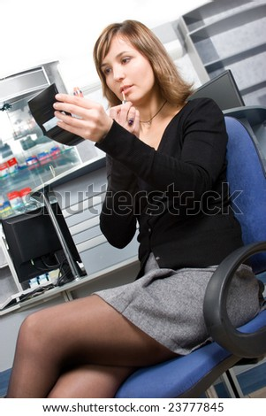 Voluptuous young business lady applying cosmetics at workplace
