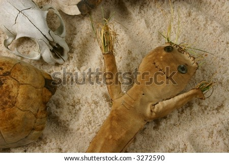 Voodoo doll and skull in sand